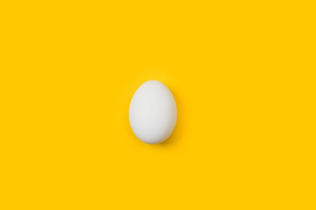 Uovo bianco su sfondo giallo