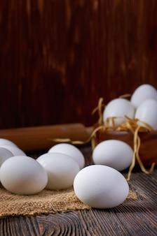 Uova bianche su tela da imballaggio e sulla tavola di legno. sullo sfondo sono le uova in una ciotola di legno e un mattarello. chiave di basso.