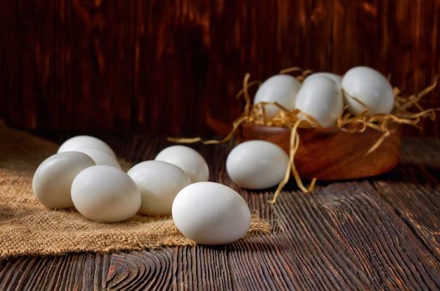 Uova bianche su una tela da imballaggio e una tavola di legno, uova in una ciotola di legno nei precedenti. chiave di basso.