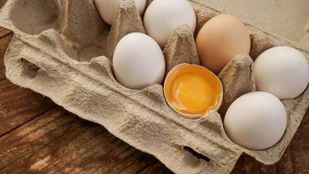 Cartone di uova bianche e metà di uovo incrinato con vista dall'alto del tuorlo su fondo di legno