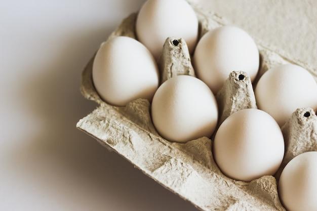 Uova bianche in una scatola di uova su una superficie bianca.