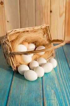 Uova bianche dal cesto sparse su un tavolo di legno turchese. i prodotti dell'azienda agricola.