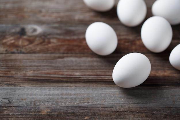 Uova bianche sul vecchio tavolo di legno