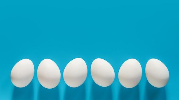 Uova bianche in fila su sfondo blu con spazio di copia
