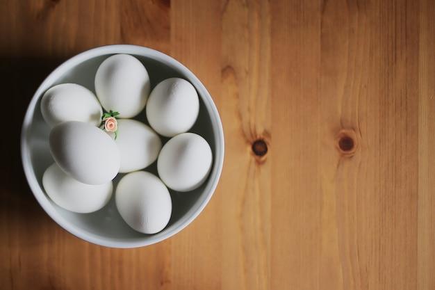 Uova bianche in un piatto bianco con roselline rosa. buona pasqua.