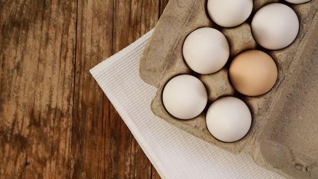 Uova bianche su fondo di legno. concetto di cucina per la colazione di pasqua e cibo sano