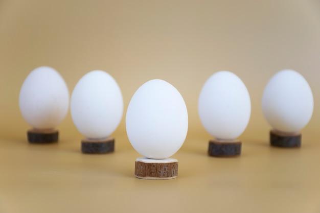 Uova bianche su anelli di legno su beige