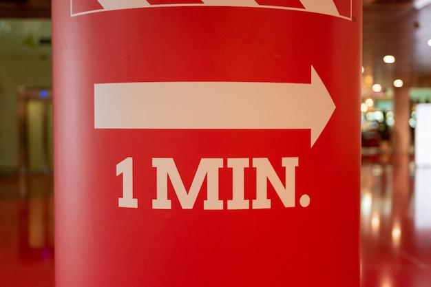Freccia di uscita di emergenza bianca su sfondo rosso.