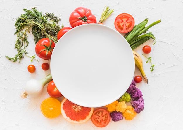 Cornice bianca vuota sopra le verdure colorate sullo sfondo