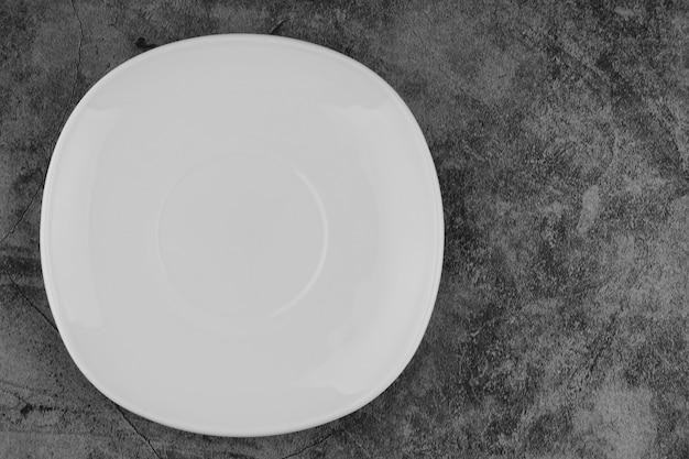 Piatto vuoto bianco su sfondo grigio