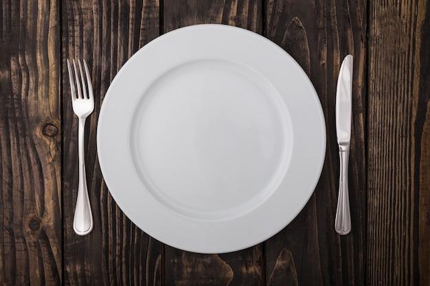 Piatto vuoto bianco, coltello e forchetta serviti sul tavolo