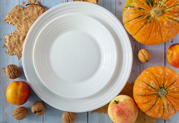 Piatti vuoti in porcellana bianca di zucca, noci, mele e nettarine con foglie autunnali