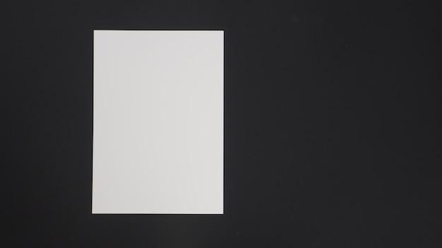 Spazio vuoto bianco carta a4 messa su sfondo nero.
