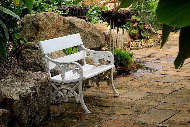 Panca vintage vuota bianca in un giardino tropicale