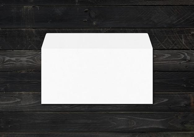Modello di mockup di busta bianca isolato su legno nero