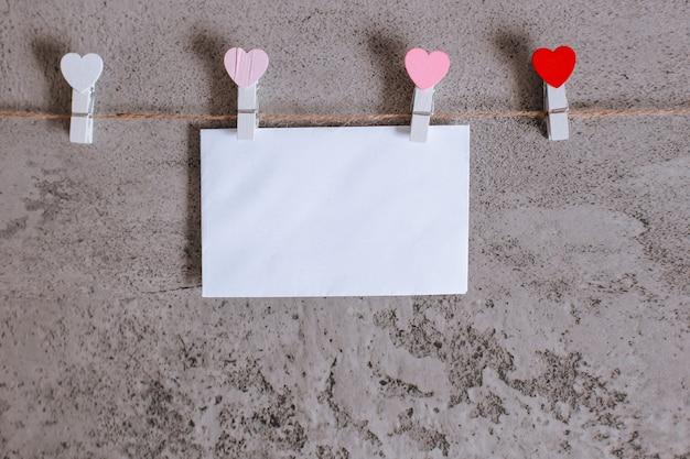Busta bianca pizzicata sulla corda della linea di vestiti a forma di mini cuore