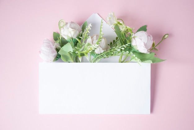 Busta bianca con fiori all'interno su sfondo rosa chiaro