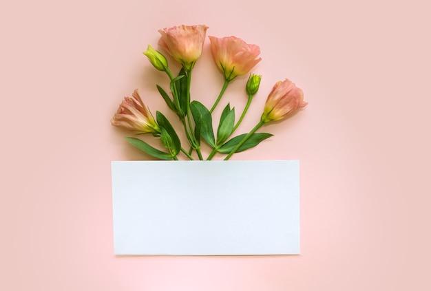 Busta bianca con fiori dietro su sfondo rosa. lay piatto. concetto di amore. focalizzazione morbida