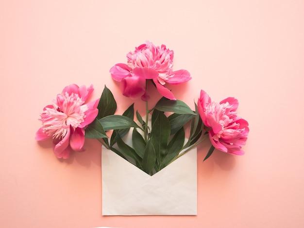 Busta bianca con peonie rosa all'interno su sfondo rosa. modello per newsletter e altri progetti di posta.