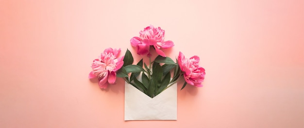 Busta bianca con peonie rosa all'interno su un modello di sfondo rosa per newsletter e altra posta