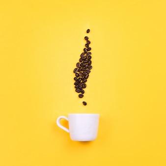 Tazza bianca del caffè espresso con i fagioli nella forma del vapore del caffè, fondo giallo. disteso