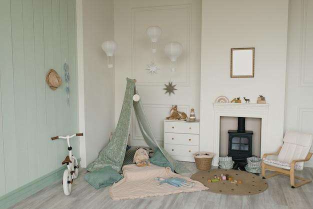 Teepee in tessuto bianco e arredamento semplice scandinavo all'interno della stanza dei bambini. bicicletta per bambini, cassettiera e caminetto con seggiolino