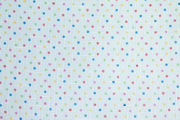 Tessuto bianco con piccoli pois multicolori. sfondo e trama del tessuto per il design