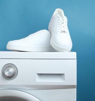Scarpe da ginnastica di moda bianche sulla lavatrice su sfondo blu