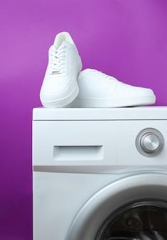 Sneaker bianche alla moda sulla lavatrice