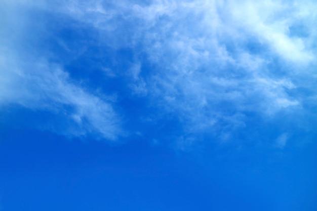 Nuvole piumate bianche si diffondono sul vibrante cielo blu