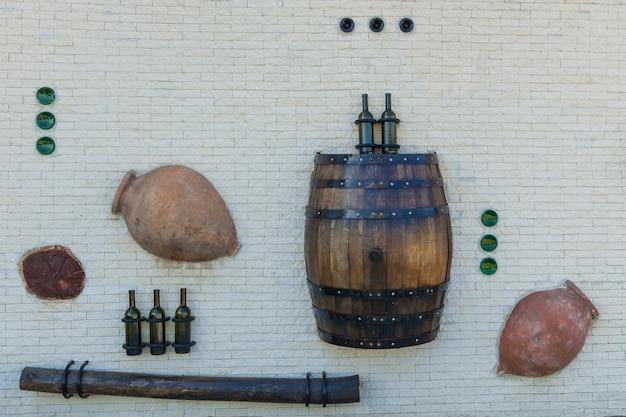 Recinto bianco da una pietra con bottiglie di vino da una botte e taglio di albero