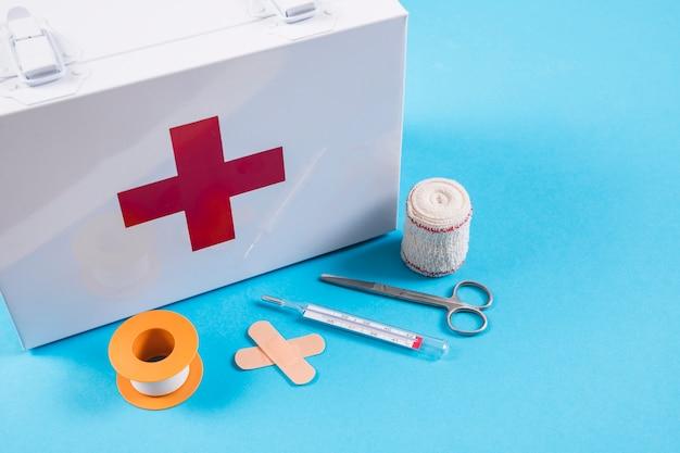Cassetta di pronto soccorso bianca con le attrezzature mediche della medicazione delle ferite su fondo blu