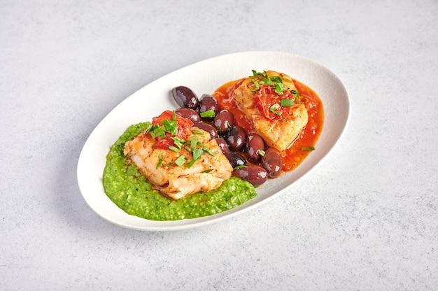 Pesce bianco con olive, pesto e salsa di pomodori e peperoni al forno sulla piastra ovale bianca, concetto di stile alimentare, close up, spazio di copia