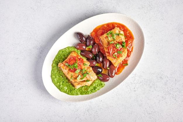 Pesce bianco con olive, pesto e salsa di pomodori e peperoni al forno su piastra ovale bianca, concetto di stile alimentare, vista dall'alto, spazio di copia