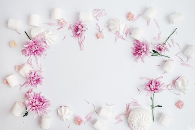Su una cornice bianca flan con fiori, marshmallow e marshmallow vista dall'alto