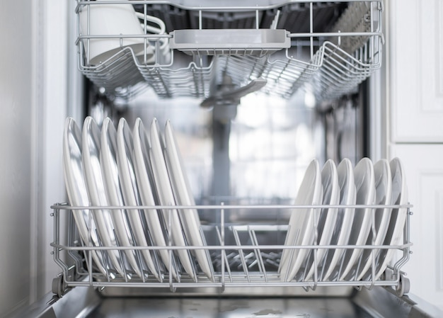 I piatti piani bianchi grandi e piccoli vengono caricati in lavastoviglie