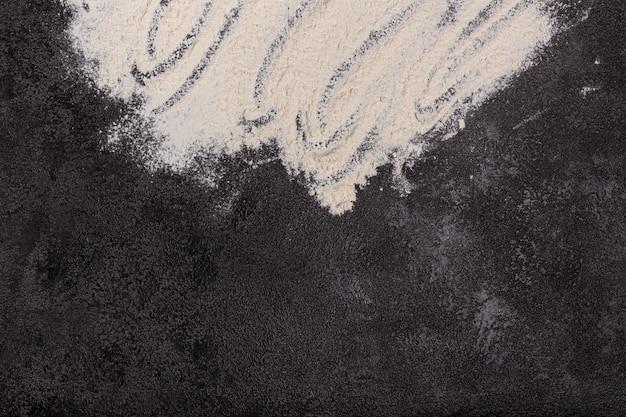 Farina bianca su fondo nero strutturale. l'inizio della cottura. processi. prodotti da forno