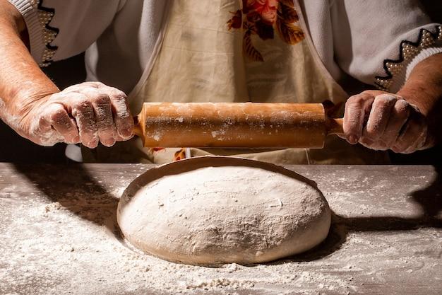 Farina bianca che vola in aria come pasticcere in abito bianco sbatte la pasta palla sul tavolo coperto di polvere bianca. concetto di natura, italia, cibo, dieta e bio