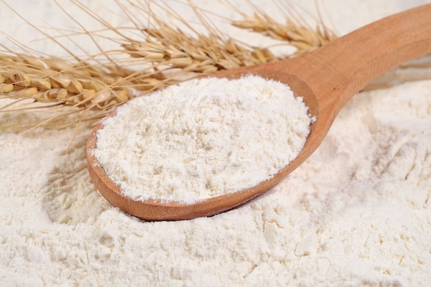 Farina bianca in un cucchiaio di legno e spighe di grano su una farina bianca