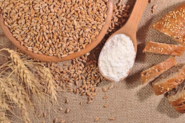 Farina bianca in un cucchiaio di legno, grano e pane su uno sfondo di saccheggio