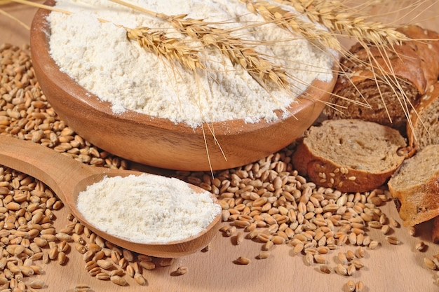 Farina bianca in un cucchiaio di legno, grano e pane su uno sfondo di legno