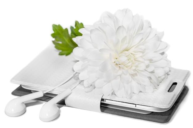 Fiore bianco di crisantemo, telefono e auricolari isolati, concetto di umore romantico o relax e armonia, umore primaverile