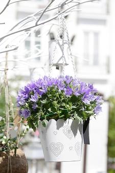 Vaso da fiori bianco con fiori viola appesi a un albero artificiale