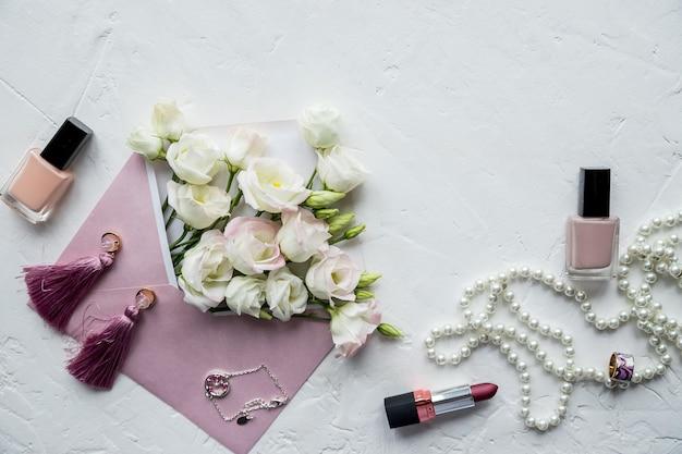 Fiori bianchi, collana di perle, profumo, biglietto di auguri su white.accessories e fiori. shopping online o concetto di incontri con lo spazio della copia.