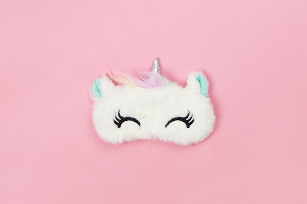 Unicorno bianco soffice pelliccia sonno maschera con gli occhi chiusi e piccole orecchie su sfondo di carta rosa pastello