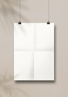 Poster bianco piegato appeso a un muro beige pulito con ombre di foglie di palma tropicale.