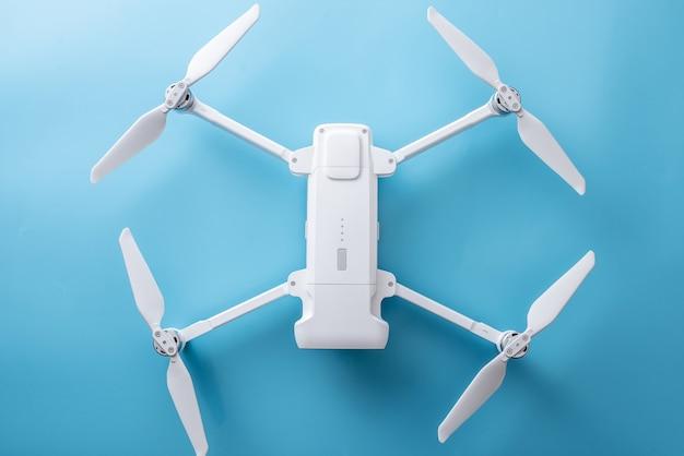 Drone quadricottero pieghevole bianco con lame sparse su sfondo blu