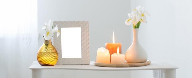 Cornice bianca, candele accese e fiori sullo scaffale su sfondo bianco