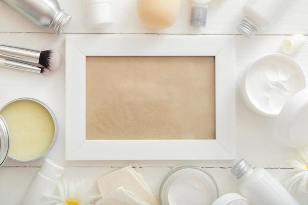 Cornice bianca con prodotti cosmetici in confezione mockup bianca su fiori da tavola in legno, borsa per cosmetici. bellezza cura della pelle trattamento dei capelli crema idratante cosmetica crema corpo burro sapone shampoo. primo piano piatto
