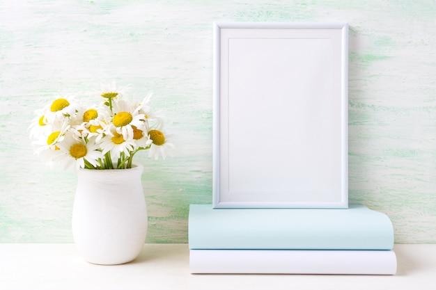 Cornice bianca con bouquet di camomilla in vaso rustico e libri